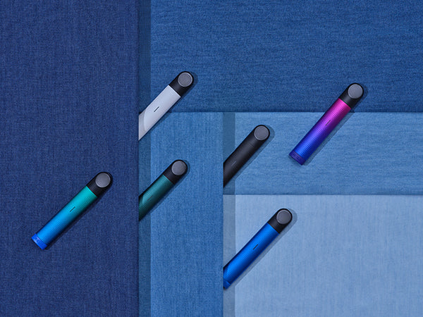 Six multicolored RELX Essential devices in a creative flat lay, shot from overhead view