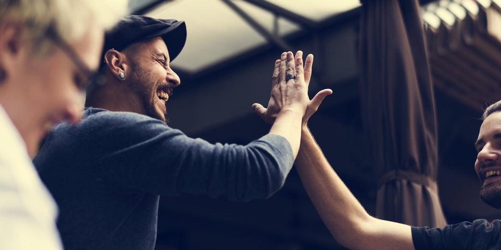 Two men high-five with each other