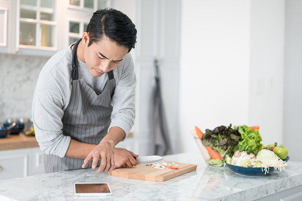 A man reading his tablet with a pensive thoughtful look while standing in his kitchen preparing a meal from a variety of fresh vegetables on the counter