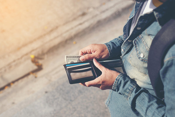 A man's hands holding wallet with credit cards and stack of money