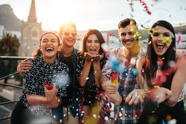 Group of friends enjoying party and throwing confetti