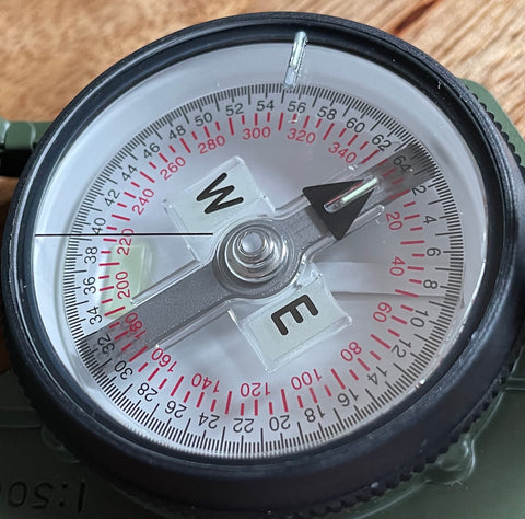 Cammenga Military Tritium Lensatic Compass, top view showing the dial, needle, markers and dual gradations.
