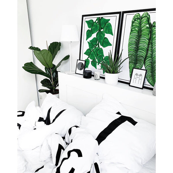 Anthurium Veitchii and heart leaf philodendron artworks hanging together above a bed