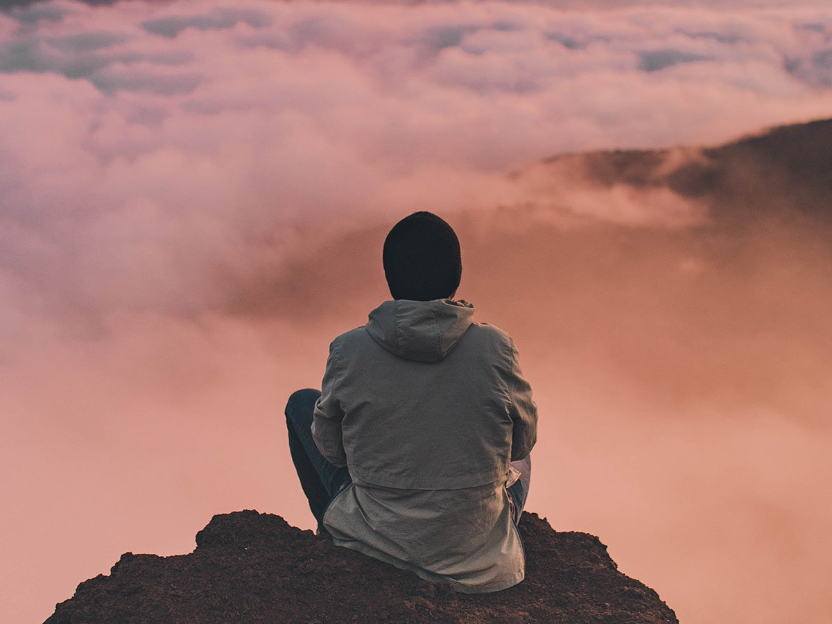 A person meditating outside on the rocks with a gorgeous sunset in front of them.