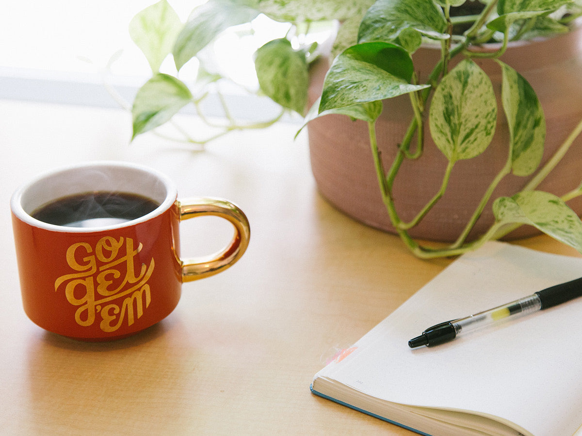 A notebook and pen sitting on a table next to a coffee mug.