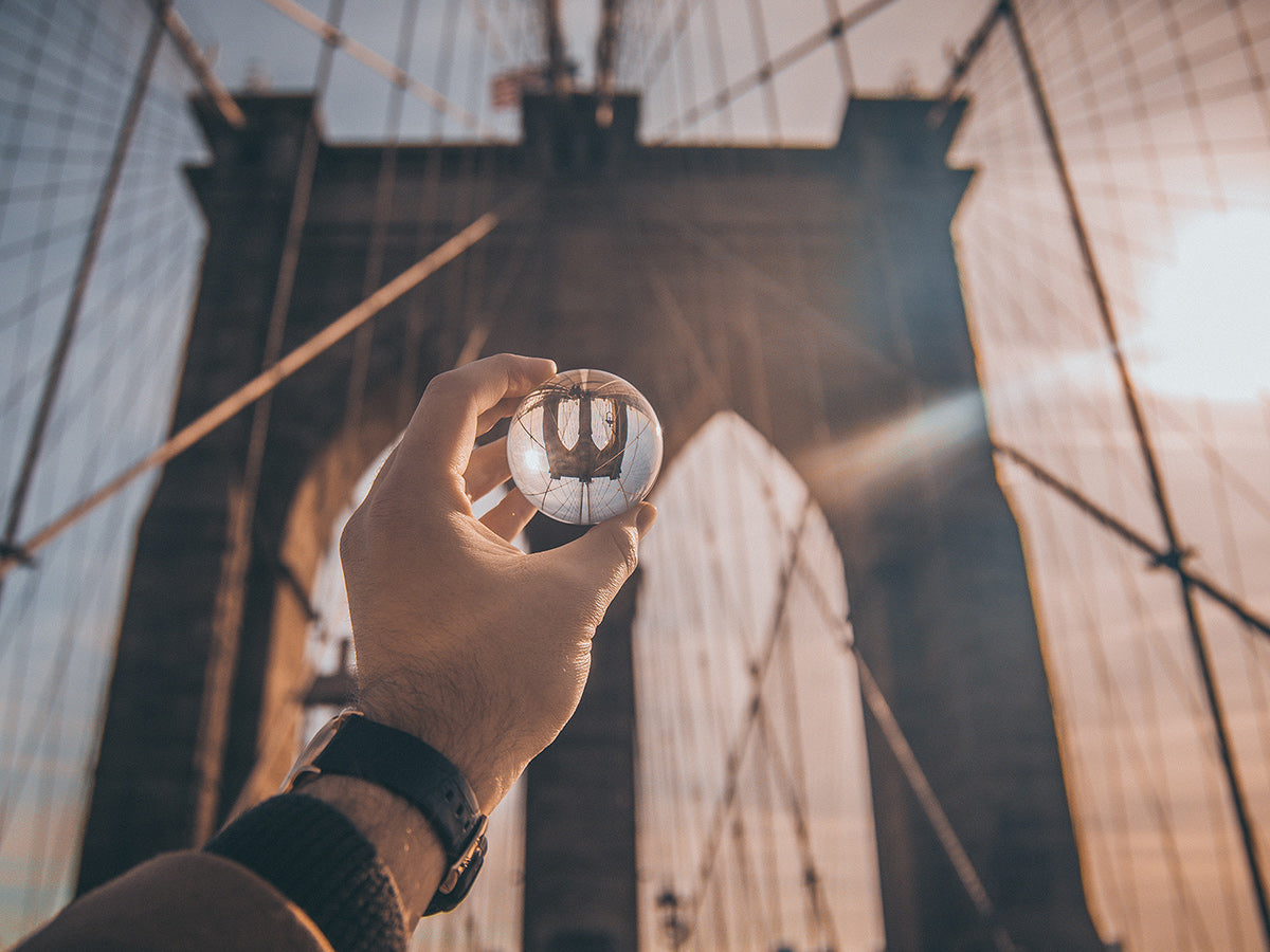 A person holding a glass ball up to the Brooklyn Bridge, changing it's perspective.