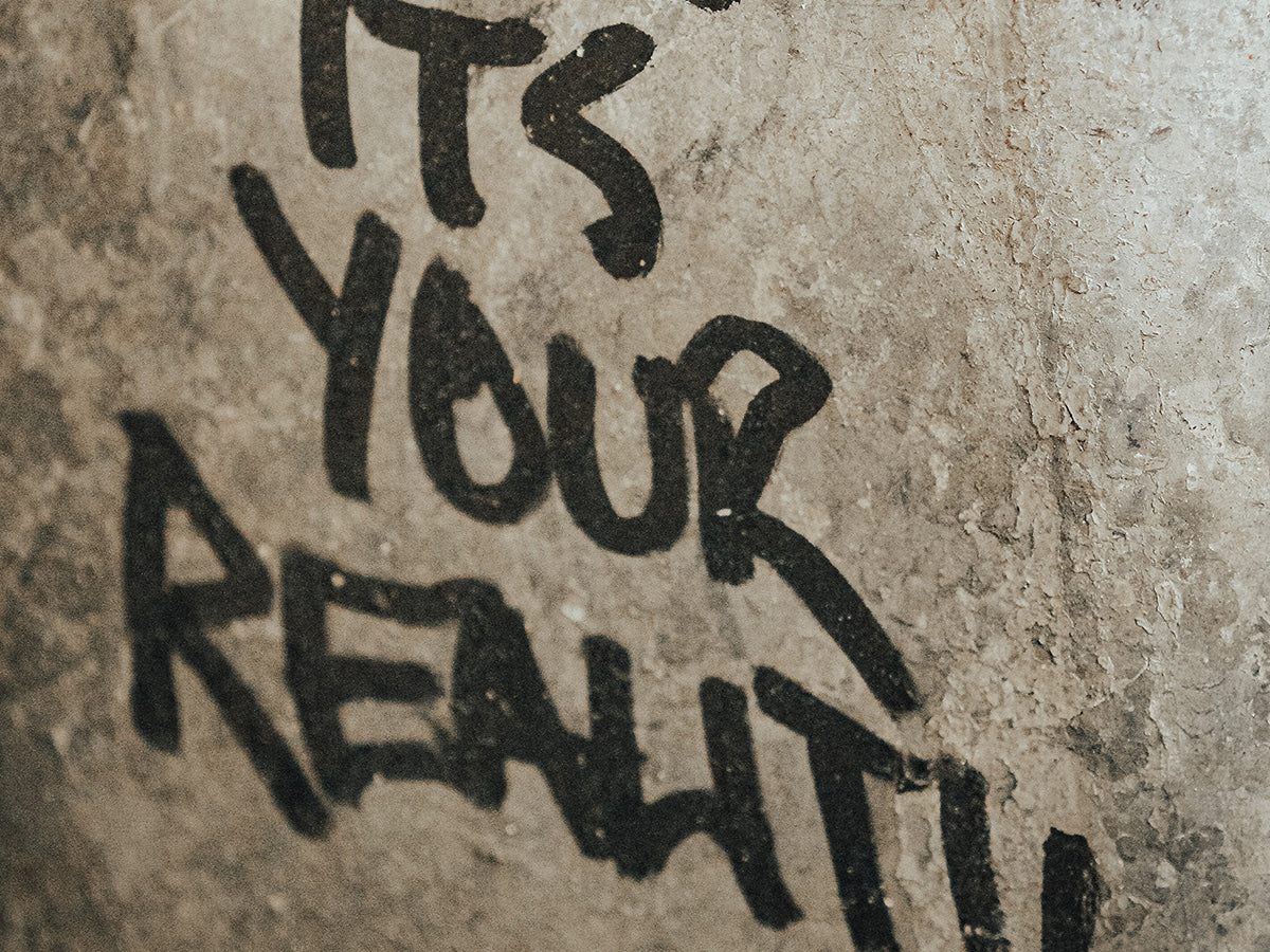 """A wall with the words """"dream until its your reality"""" tagged on it."""