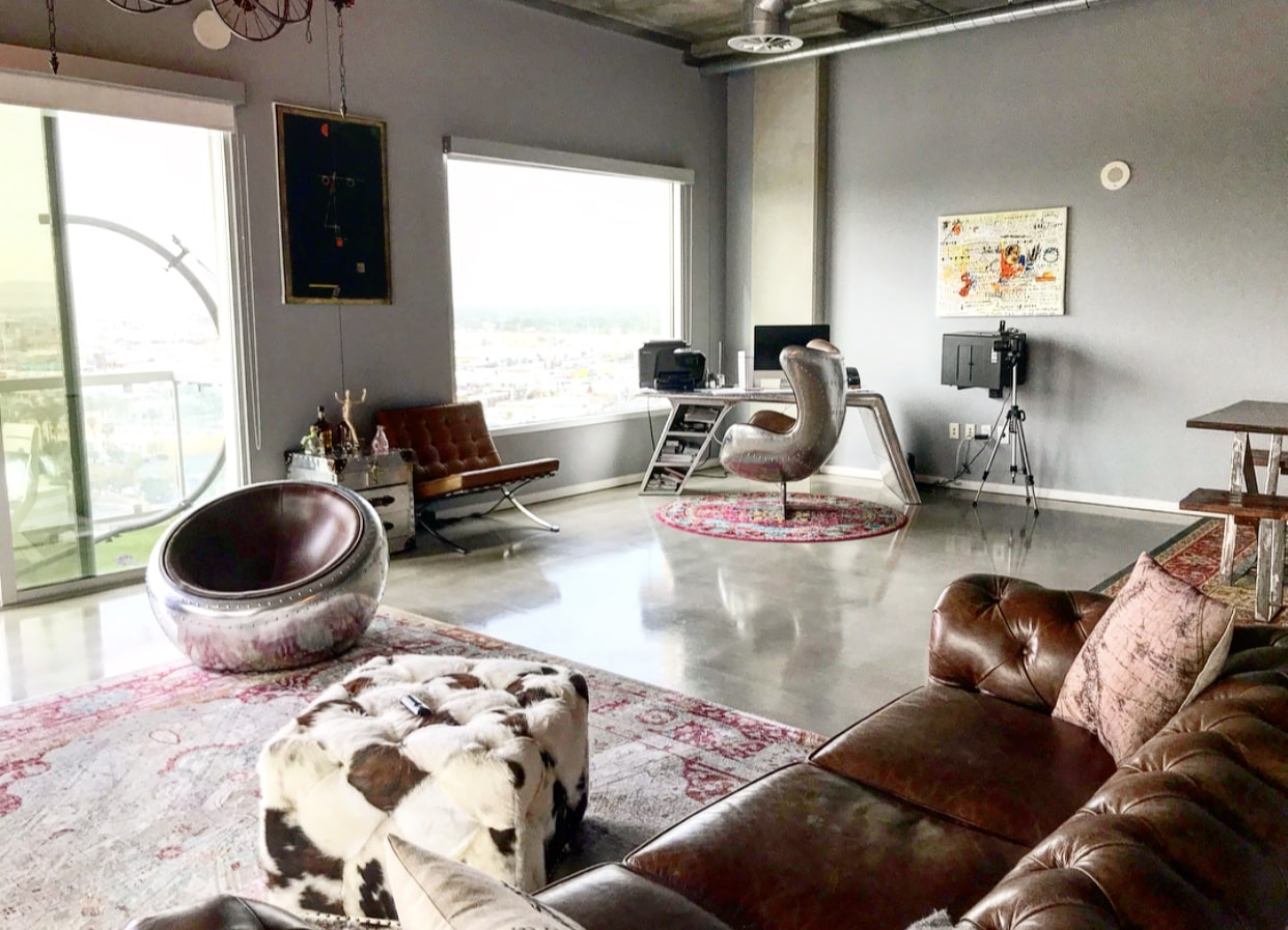 0Industrial livingroom with furniture in the style of vintage orb and egg chairs, barcelona chair, chesterfield sofa, cow hide pouf, with modern boho rugs and vintage decor on the walls.
