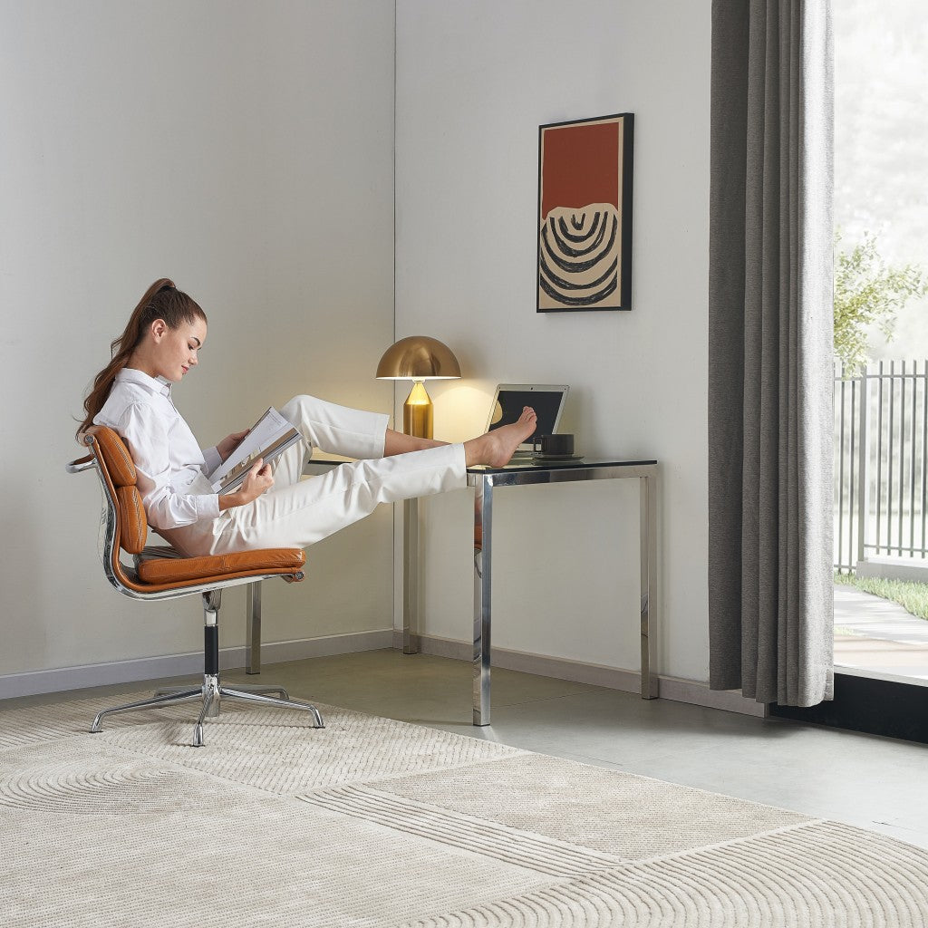 woman sitting in a stylish, modern, leather office chair reading a magazine with feet up on a sleek, modern desk.