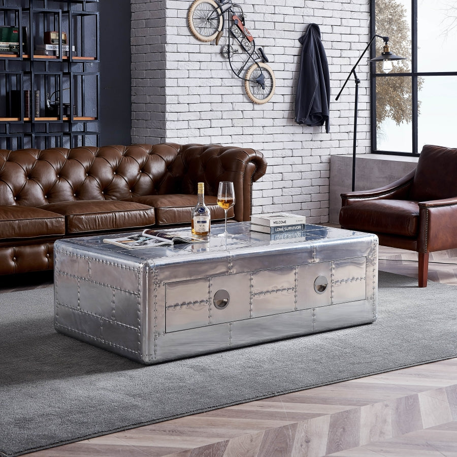 An industrial coffee table with drawers is centered in an industrial room with retro decor. There is a vintage chair and chesterfield sofa in brown leather and an industrial bookcase.