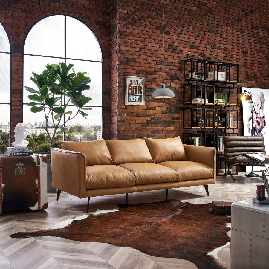 Industrial furniture and vintage decor. Brown leather couch and chair. Cowhide trunk and rug, metal industrial caninet, bookshelf, industrial lamps.