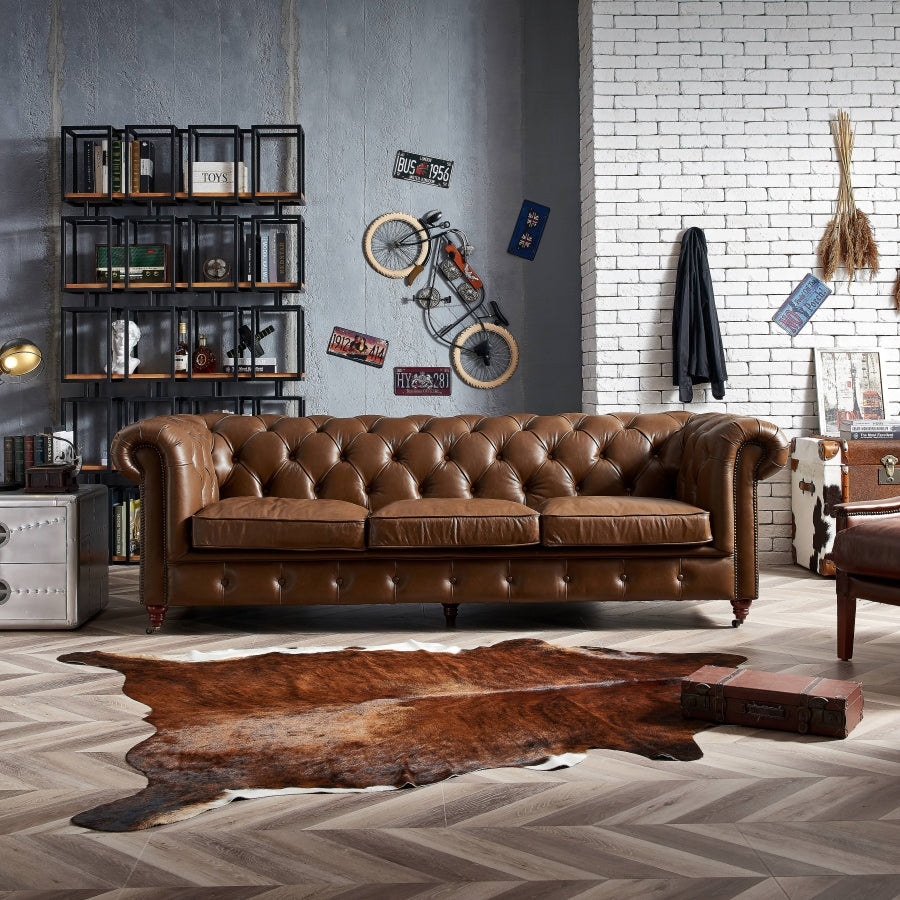 Industrial furniture and vintage decor in modern space. A chesterfield sofa is centered with an industrial bookcase in the background and a cowhide rug in front. Accents include a cowhide trunk, industrial cabinet with riveted metal, and industrial lamp.