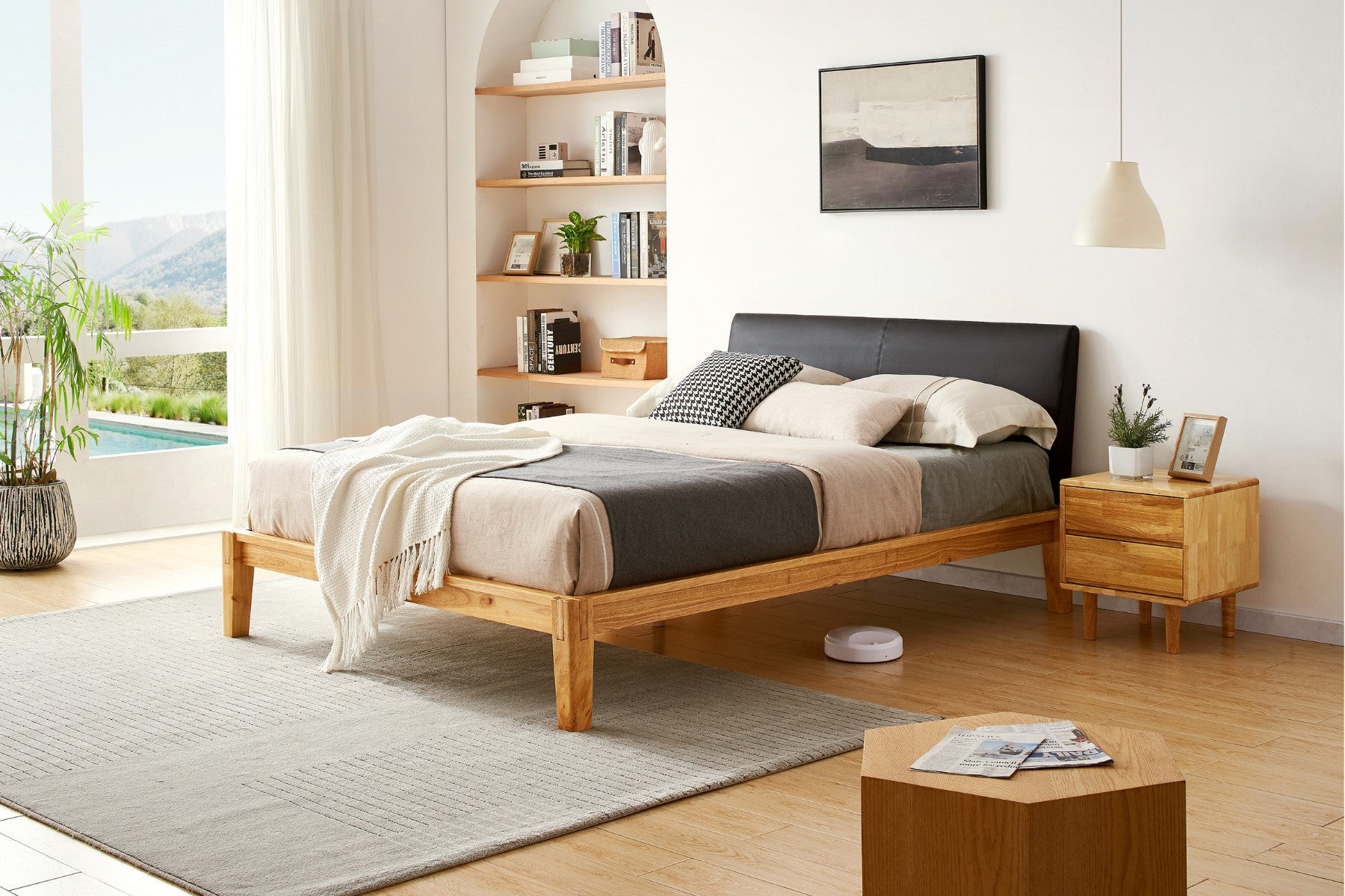A bed with warm, wooden frame, and black cushioned headboard is styled with bedding in cream, white, black, and grey.