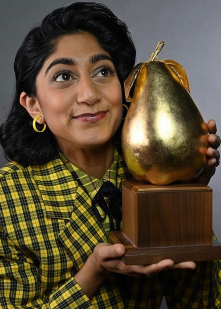 Sunita Mani wearing plaid with a pear award