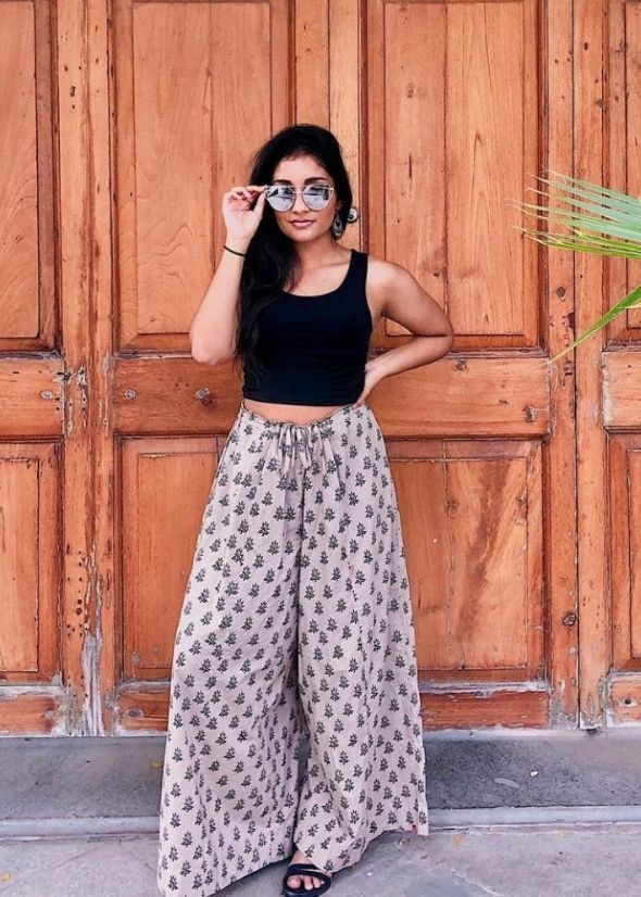 Nivita Sriram wearing printed pants in front of a wooden door