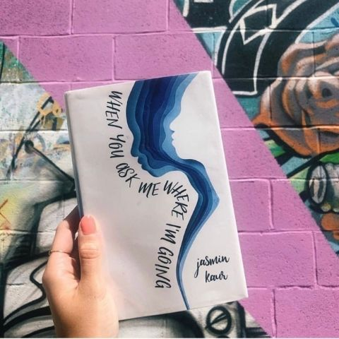 When you ask me where I'm going by Jasmin Kaur book against a mural