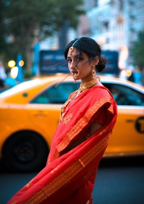 Afshan Nasseri in a red saree posing in front of a yellow car