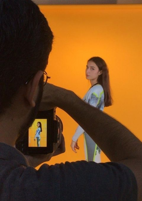 Rameen Saad modeling with an orange background