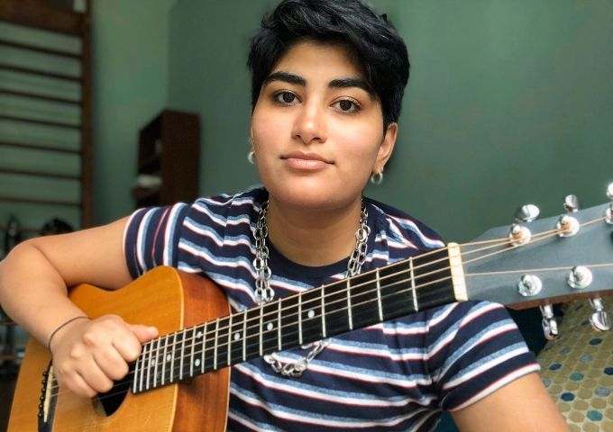 Somaya Music with a guiter and wearing a striped shirt