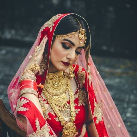 South Asian bride wearing red and gold