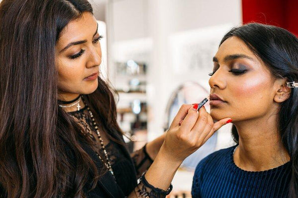 image of Vithya Visvendra applying lip color on a model