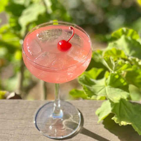Light pink cocktail with maraschino cherry