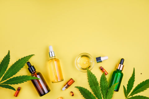 Marijuana leaves and tinctures on a yellow background.