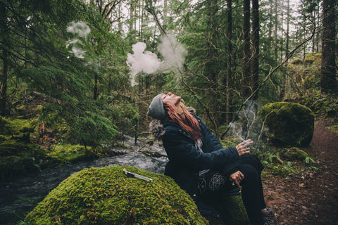 A girl smoking weed in the forest.