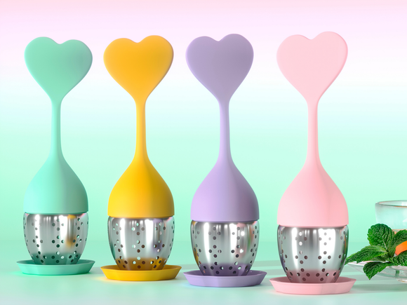 image of all four colour heart shape silicon and stainless steel tea infusers tea strainer and a peppermint tea in the background