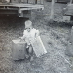 Daryl as a young beekeeper carrying empty honey tins