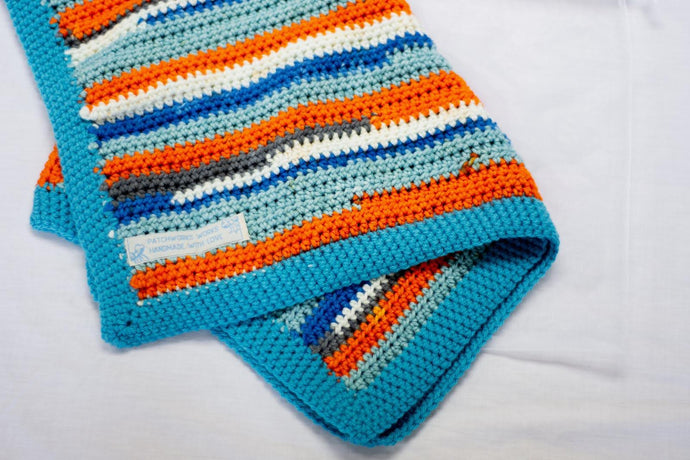Blue Stripe baby blanket by Flutterbys and Pretticoats, blues, grey, orange and white stripes handcrocheted, fit for a prince!