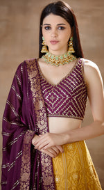 Purple embroidered blouse with yellow lucknawi lehenga paired with purple banarsi dupatta.