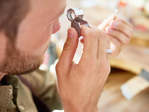An image of a man looking through an eyepiece at jewelry.