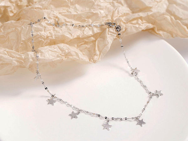 An image of a silver, choker-style necklace with stars.