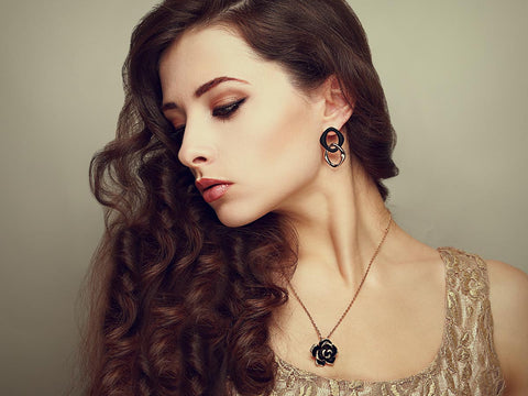 An image of a woman showing off her earrings and her necklace.