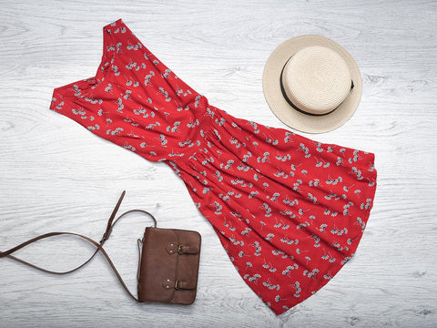 An image of a sun hat, red dress, and brown purse laying on the floor.