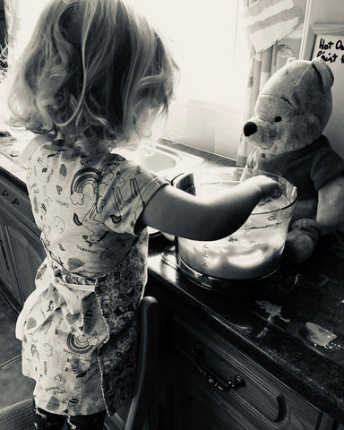 girl standing backwards on a chair baking with grandma