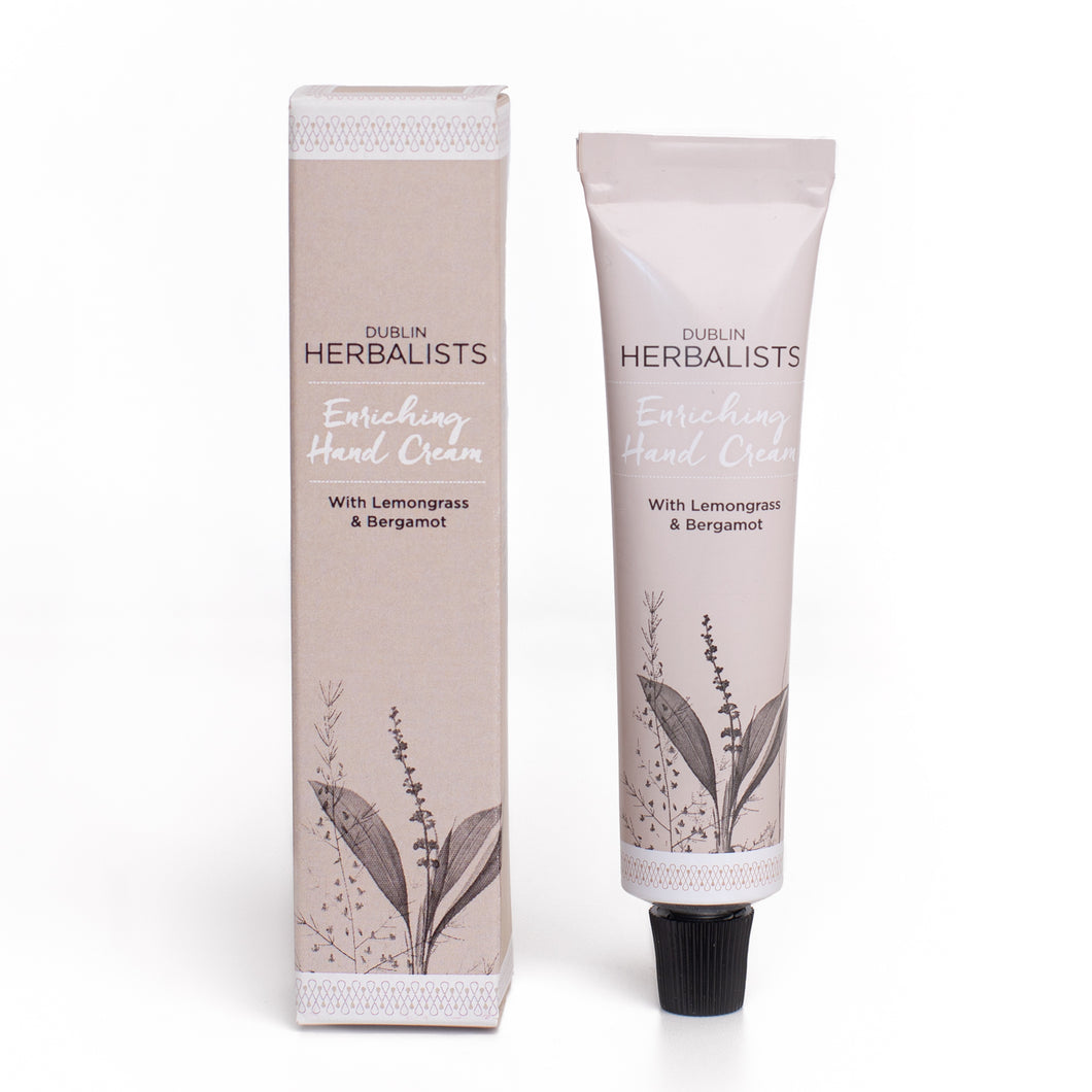 A taupe tube with black lid and Dublin Herbalists writing in black and Enriching Hand cream written in white. A taupe box and Dublin Herbalists writing in black and Enriching Hand cream written in white.