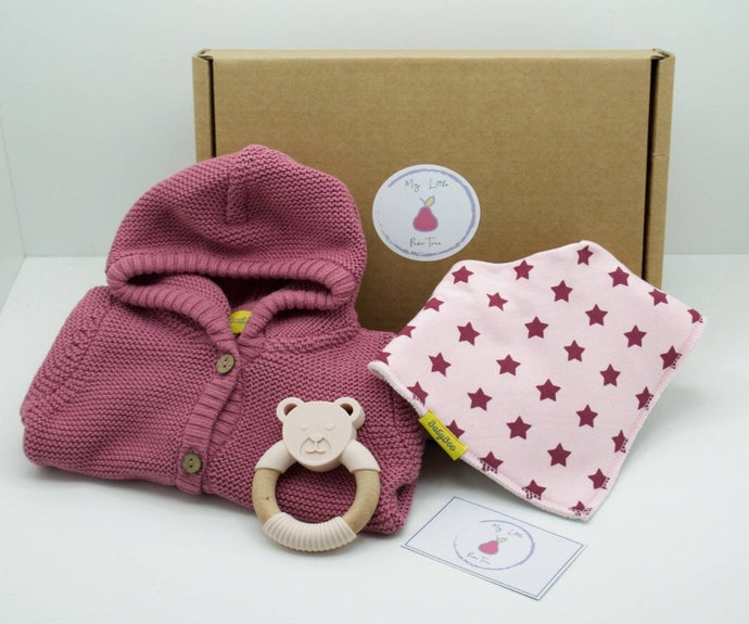 Natural coloured gift box with the My Little Pear Tree logo circular sticker on the lid, the sticker has a purple boarder with a pink pear in the centre with the writing My little Pear Tree, a pink coloured hooded knitted cardigan, light pink bandana bib with pink stars, natural silicone and wooden bear teether and a My Little Pear Tree card.