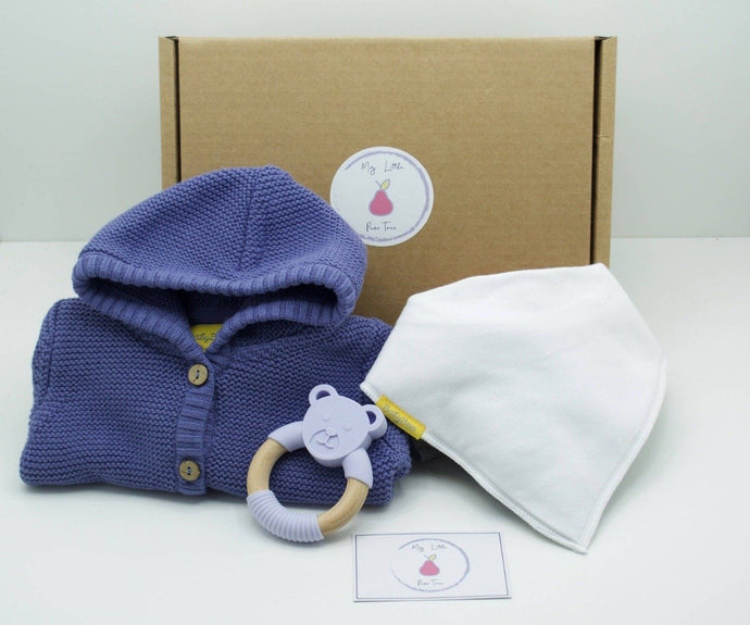 Natural coloured gift box with the My Little Pear Tree logo circular sticker on the lid, the sticker has a purple boarder with a pink pear in the centre with the writing My little Pear Tree, a periwinkle colour hooded knitted cardigan, a plain white  bandana bib, a silicone and beech lilac bear teether and a My Little Pear Tree card.