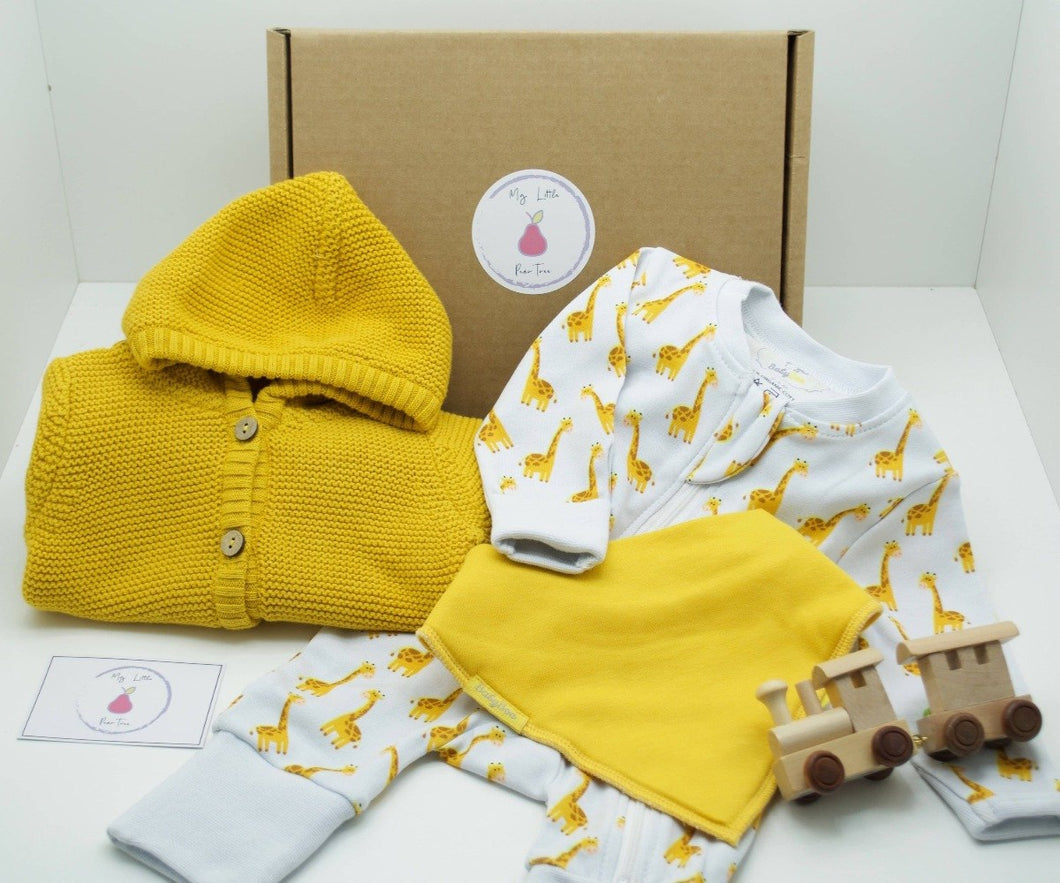Natural coloured gift box with the My Little Pear Tree logo circular sticker on the lid, the sticker has a purple boarder with a pink pear in the centre with the writing My little Pear Tree, a zip up white babygrow with yellow giraffe pattern, a yellow knitted hooded cardigan, a yellow bandana style bib, a wooden train with a carriage and a My Little Pear Tree card.