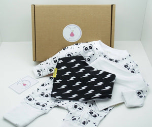 Natural coloured gift box with the My Little Pear Tree logo circular sticker on the lid, the sticker has a purple boarder with a pink pear in the centre with the writing My little Pear Tree, a zip up white babygrow with panda faces all over the babygrow, a black bandana style bib with white lightning strike pattern, a plain white bandana style bib and a My Little Pear Tree card.
