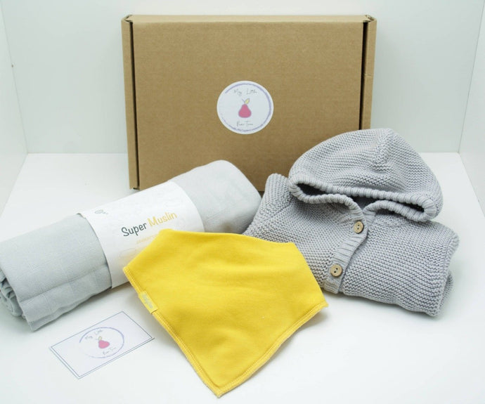 Natural coloured gift box with the My Little Pear Tree logo circular sticker on the lid, the sticker has a purple boarder with a pink pear in the centre with the writing My little Pear Tree, a grey knitted hooded cardigan, a yellow bandana style bib, a grey muslin cloth and a My Little Pear Tree card.