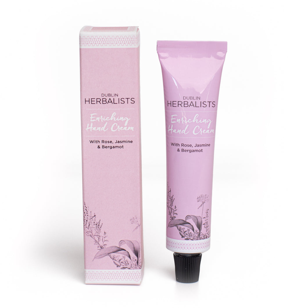 A pink tube with black lid and Dublin Herbalists writing in black and Enriching Hand cream written in white. A pink box and Dublin Herbalists writing in black and Enriching Hand cream written in white.