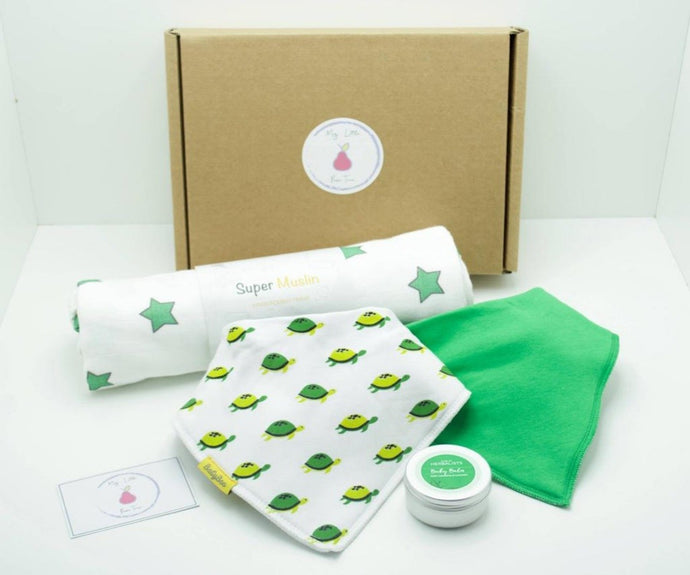 Natural coloured gift box with the My Little Pear Tree logo circular sticker on the lid, the sticker has a purple boarder with a pink pear in the centre with the writing My little Pear Tree, a white  bandana style bib with green and yellow turtle pattern, a plain green bandana bib, a white muslin cloth with green and yellow turtles, a silver tin of baby calm with a green label on the lid and a My Little Pear Tree card.
