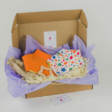 Load image into Gallery viewer, gift box including a white with multi colour star bandana style bib, orange bandana style bib and star beech wood teether