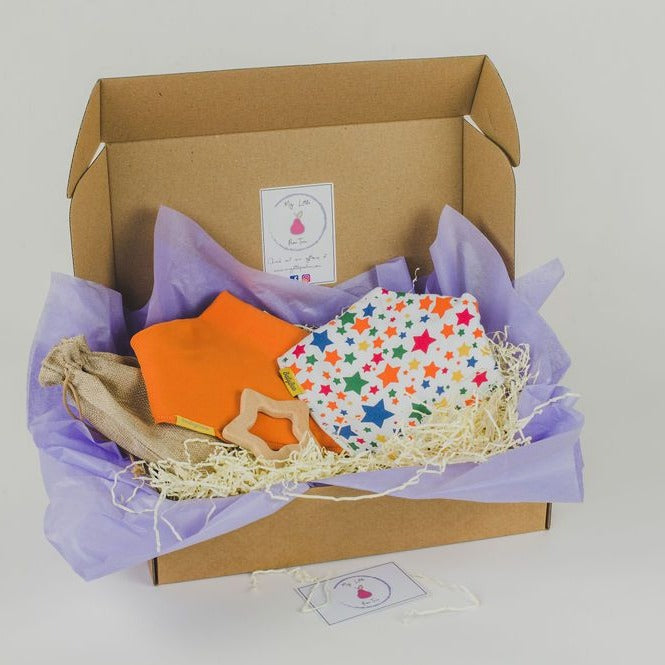 gift box including a white with multi colour star bandana style bib, orange bandana style bib and star beech wood teether