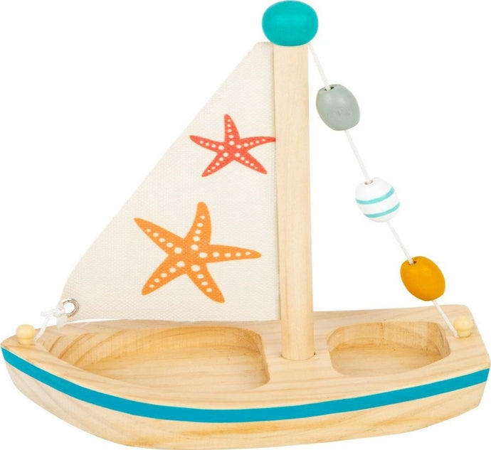 a small wooden sail boat with an orange starfish and red starfish on the sail