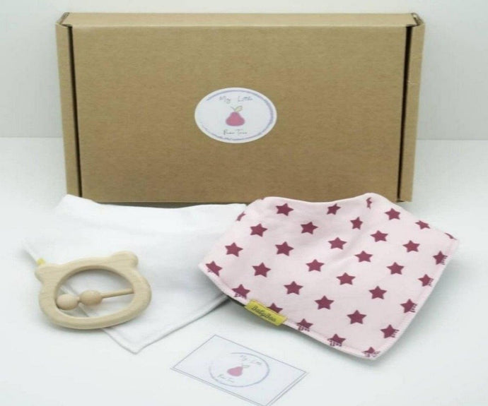 Natural coloured gift box with the My Little Pear Tree logo circular sticker on the lid, the sticker has a purple boarder with a pink pear in the centre with the writing My little Pear Tree, a plain white bandana style bib, a pale pink with dark pink stars bandana bib, a light wooden colour bear shaped rattle teether and a My Little Pear Tree card.