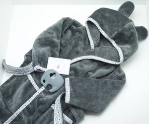 A dark grey bathrobe with ears on the hood and a light grey trim with an elephant pattern, also a grey elephant shaped silicone teether